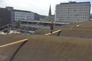 Um das Dach bei der Arbeit besser begehen zu können, verlegten die Dachdecker Bohlen zwischen den gewölbten Dachabschnitten