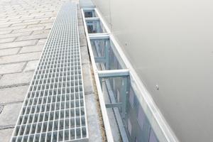 Großflächige Öffnungen am fassadenseitigen Bereich der Rinne sowie die hervorkragenden Auflageflächen für die Roste und der ebenso weit hervorstehende Rinnensockel sorgen für ausreichenden Abstand zur Fassade und einen gut durchlüfteten Wandanschluss
