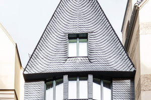 Die Giebelfront ist vom zentralen Fenster aus nach links und rechts mit Schieferschindeln eingedeckt