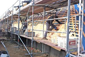 Die Handwerker befestigten drei Lagen Alaska-Zedernholzschindeln mit Druckluftnaglern an der Fassade
