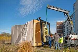 """Das wärmegedämmte Stufenfalzglas für die Frontseite des """"Timber Prototype House"""" wird per Autokran eingehoben und montiertFoto: IBA Thüringen/Thomas Müller"""