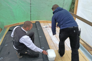 Oliver Glöckner von Carlisle (rechts) trägt den Flächenkleber für die Dachbahn mit einer Farbwalze auf