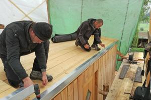 """Letzte Vorbereitungen der Dachfläche: Die Dachrandbleche werden von Oliver Karolius (links) und Holger Längle bündig an die Dachkante geschraubt <span class=""""bildnachweis"""">Fotos: Rüdiger Sinn</span>"""
