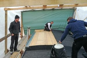 Die Plane des höher gelegenen Dachteils wird von den Handwerkern aufgelegt und in der gleichen Arbeitsabfolge wie die Plane zuvor befestigt
