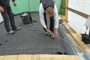 Rechts: Um die Blechaufkantungen in die Dachplane einzubinden, wird der Kontaktkleber beidseitig aufgesprüht