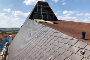Auf der flach geneigten Dachfläche sind noch die alten Bitumenschindeln zu sehen, seitlich schon die neuen Aluminiumdachschindeln