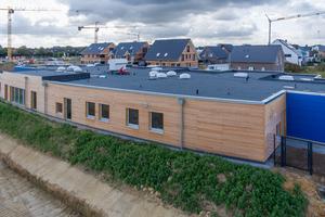 """Außenansicht der Kita Korschenbroich von Norden mit Sicht auf die Holzfassade an der zukünftigen Hauptstraße des Baugebiets """"An der Niers-Aue""""<br />"""