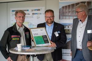 Übergabe des Zertifikats der CO₂ -Bank über die Speicherung von 151 t CO2 durch den Bau der 5-Gruppen Kita in Korschenbroich an Marc Venten, Bürgermeister der Stadt Korschenbroich<br />