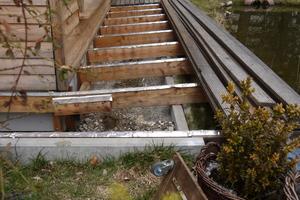 Links unten: Die Setzung des Gebäudes ist klar erkennbar: Die Schraubfundamente sind eingesunken, das Streifenfundament für die Terrassenauflage geblieben