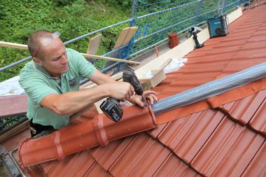 First- und Gratrollen schützen die Dachkonstruktion vor Schnee und Treibregen, hier werden gerade die Gratziegel verschraubt