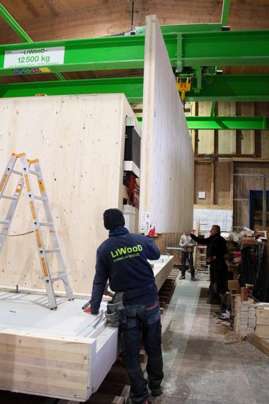 Eine Brettsperrholzwand wird in der Werkhalle eingehoben und montiertFoto: Franziska Vogl/Liwood