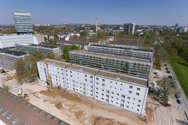 """Aufstockung wie am Fließband: Die ersten drei Häuser vorne im Bild sind schon aufgestockt, dahinter sind die Bestandsgebäude mit Satteldächern zu sehen<span class=""""bildnachweis"""">Foto: Liwood/Skycamera</span>"""