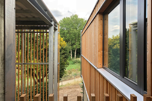 Die Fassade des aufgestockten Geschosses besteht aus einer Lärchenholzschalung mit unterschiedlich breiten und tiefen Latten, die im wilden Verband montiert sind