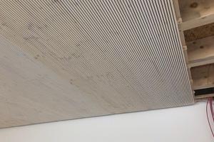 In den Klassenräumen reduzieren Akustikdecken aus geschlitzten Dreischichtplatten mit Holzfaserdämmung den Lärmpegel