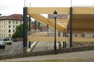 In den schmalen Teilen des Gebäudes bilden horizontal verlegte Holzträger eine Zwischenebene. Sie sind an schwarzen Stahlträgern abgehängt