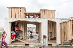 """Die Kinder des Waisenhauses """"Our Bridge"""" in Xhanke (Nordirak) spielen in einem mit Robinienholz zum Spielplatz umgebauten Seefrachtcontainer"""