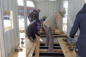 Gemeinsam mit Studenten aus Lüneburg bauen die Spielplatzbauer einen Robinienholzboden in den Container ein<br /><br />