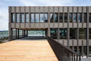 """Das Schulerweiterungsgebäude in Nottwil: Über zwei Zugangsstege aus Lärchenholz ist der Neubau mit der bestehenden Schule verbunden<span class=""""bildnachweis"""">Fotos: Kost Holzbau und Gesamtbau</span>"""