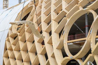 Ein gewundener Brettschichtholzträger wird eingehoben und montiert. Die Träger sind teilweise in zwei Richtungen gekrümmt