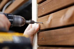 Die Schraube zieht die Kebony-Holzleisten fest an die Unterkonstruktion