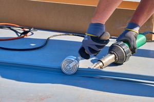 Auf den zum Schulhof geneigten Pultdachflächen verschweißten die Dachdecker PIB-Stehfalzprofile