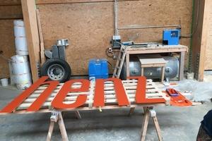 Die einzelnen Buchstaben des Schriftzuges wurden auf Maschinen von Holzbau Henz aus den Faserzementpaneele ausgeschnitten und farblich behandelt