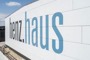 Der Firmenschriftzug an der Giebelseite der neuen Werkhalle von Holzbau Henz in blau und schwarz