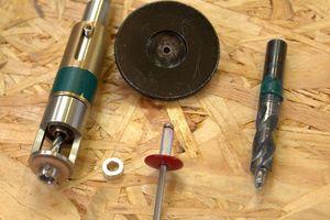 Bohr- und Niet-utensilien für die Montage: rechts der Stufenbohrer (9,5 mm), daneben ein farbiger Fassadenniet mit Festpunkthülse, ein Sonderlehrenmundstück für das Nietgerät und links eine Einhandfeder-Bohrvorrichtung mit 5,1 mm-Bohrer für zentriertes Bohren in der Unterkonstruktion