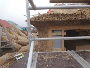 Am Übergang von der Fassade zum Dach entstand eine dichte, saubere Kante aus geklopften Reetbündeln