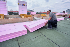 Umkehrdach: Ein Dachdecker verlegt XPS-Dämmplatten auf der Dachabdichtung