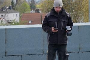 Ein Dachdecker kontrolliert den Dachaufbau mit Scanner und Smartphone in der Hand