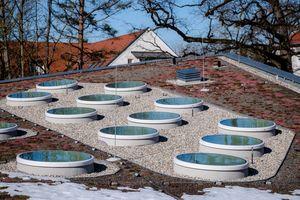 """22 runde Flachdachfenster """"F100"""" von Lamilux mit jeweils 1,5 m Durchmesser wurden auf dem geschwungenen Dach montiert"""