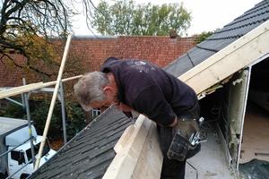 Auf den am Vortag eingebauten Wechsel montieren die Handwerker den Rahmen für das Dachfenster