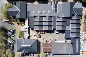 Von oben zeigt sich die unterschiedlich strukturierte Dachlandschaft des Bundesbildungszentrums des Zimmerer- und Ausbaugewerbes in Kassel. Unter den Sheddächern befinden sich die Zimmererhallen