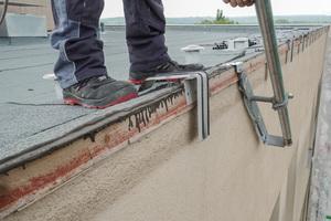 Für den Seitenschutz werden Ankerplatten in der Attika verschraubt und darin die Gerüstpfosten eingehängt