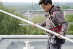 Ein Sifatec-Mitarbeiter während der Montage des Seitenschutzes, gesichert mit persönlicher Schutzausrüstung gegen Absturz