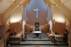 Blick in den fertigen Innenraum der Kirche. Ein Holz-Aluminium-Fenster bildet den kreuzförmigen Ausschnitt in der Giebelseite