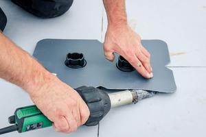 Nach dem Einmessen verschweißen die Dachdecker die Grundfüße der Solar-unterkonstruktion über Manschetten auf dem Dach