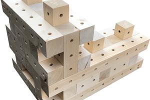 Die Holzbausteine werden mit Hartzholzdübeln in drei unterschiedlichen Richtungen zu Wänden verbunden