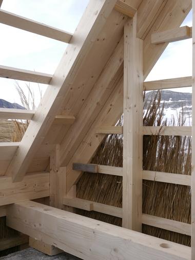 Die Holzkonstruktion der Hütte wird mit Reetbunden eingedeckt