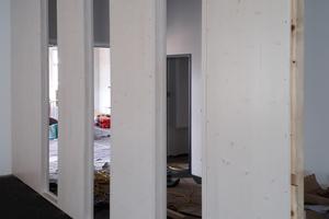 Für das Trennwandsystem stehen mehrere Bekleidungsvarianten zur Verfügung, beispielsweise eine sichtbare Holzbeplankung in lasierter Ausführung
