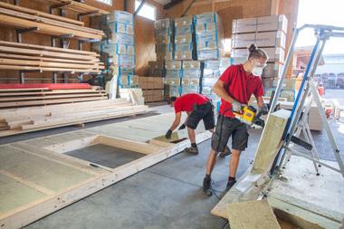 In der Vorfertigung werden die Holzständerwände mit Steinwollplatten gedämmt