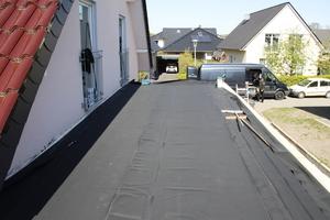 Die EPDM-Plane wird auf dem Dach verlegt und händisch der Dachform angepasst. Dann lassen die Handwerker die Plane kurz ruhen, damit sich Falten und Wellen legen können