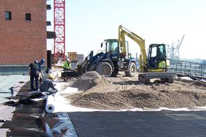 Die Dränschicht dient bereichsweise als verlorene Schalung, um ein Betonfundament setzen zu können, in diesem Fall unter den niedrigen Mauern