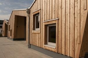 Die Kita hat ein wellenförmiges Dach. Die Fassade ist mit einer vertikalen Holzschalung und versetzt angeordneten Fenstern gestaltet