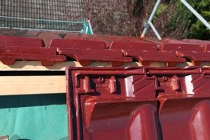 Die Firstanschlussziegel werden bis unter den Dachfirst verlegt. Durch den Verzicht auf Firstlatte und Firstrolle gewinnt man Zeit bei der Verlegung