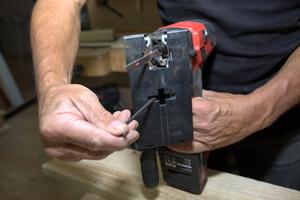Mit dem Inbusschlüssel wird eine Sechskantschraube im Sägefuß gelöst und der Gehrungswinkel auf 45 Grad eingestellt