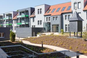 Die Fassaden&nbsp; der Gebäude wurden mit grau lasierten Biberschwanzziegeln und Schiefer in dynamischer Deckung verkleidet<br />