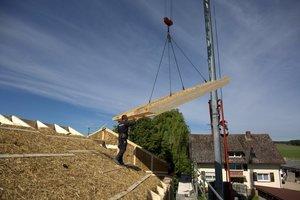 Die ersten Dachelemente sind verlegt, die nächsten schweben ein und werden von den Handwerkern montiert