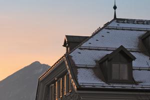 Schneefanggitter auf einem Krüppelwalmdach im alpinen Bereich verhindern ein Abrutschen der Schneemassen